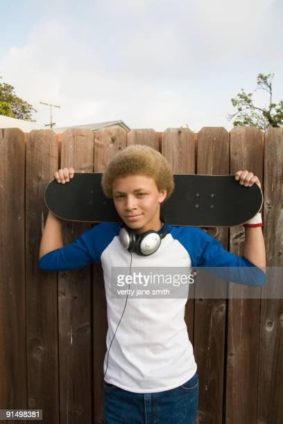 Mixed race boy in headphones holding skateboard
