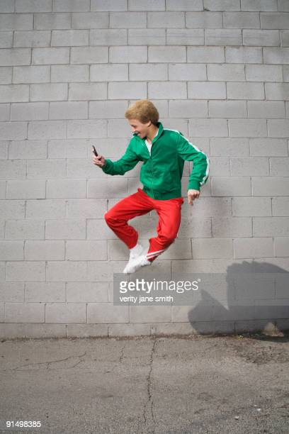 Mixed race boy jumping in mid-air using cell phone