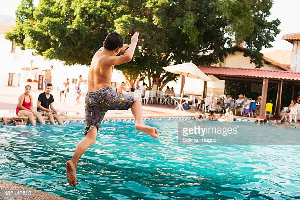 Mixed race boy jumping into pool