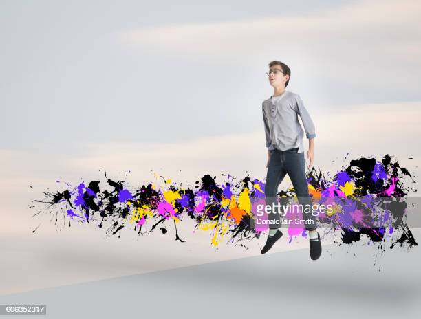 Mixed race boy jumping with paint splatters
