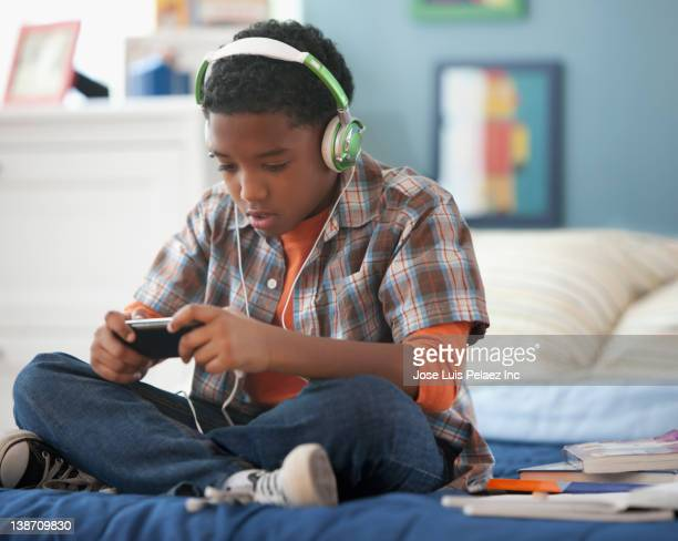 Mixed race boy listening to mp3 player