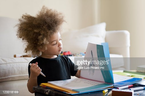 Mixed race boy looking at book in living room