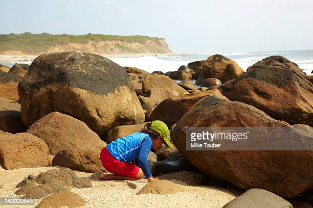 Mixed race boy looking underneath rocks