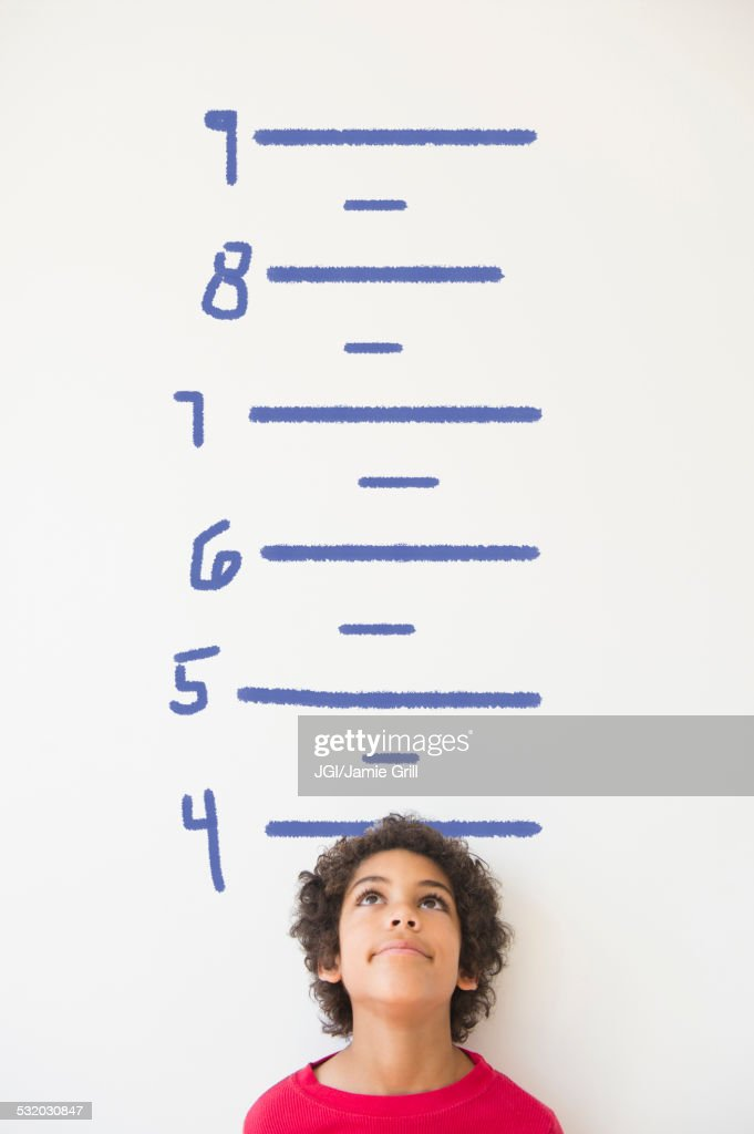 Mixed race boy measuring his height on wall chart