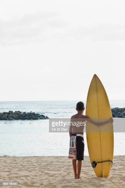 Mixed race boy on beach with surfboard