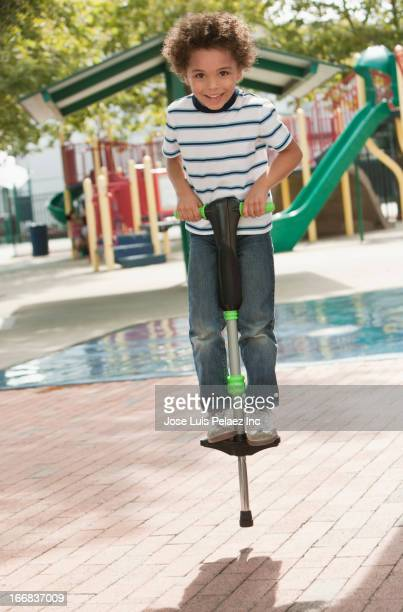 Mixed race boy on pogo stick at playground