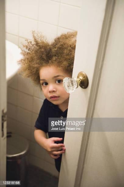 Mixed race boy opening bathroom door
