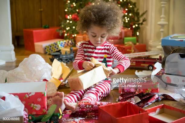 Mixed race boy opening Christmas presents