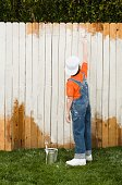 Mixed Race boy painting fence