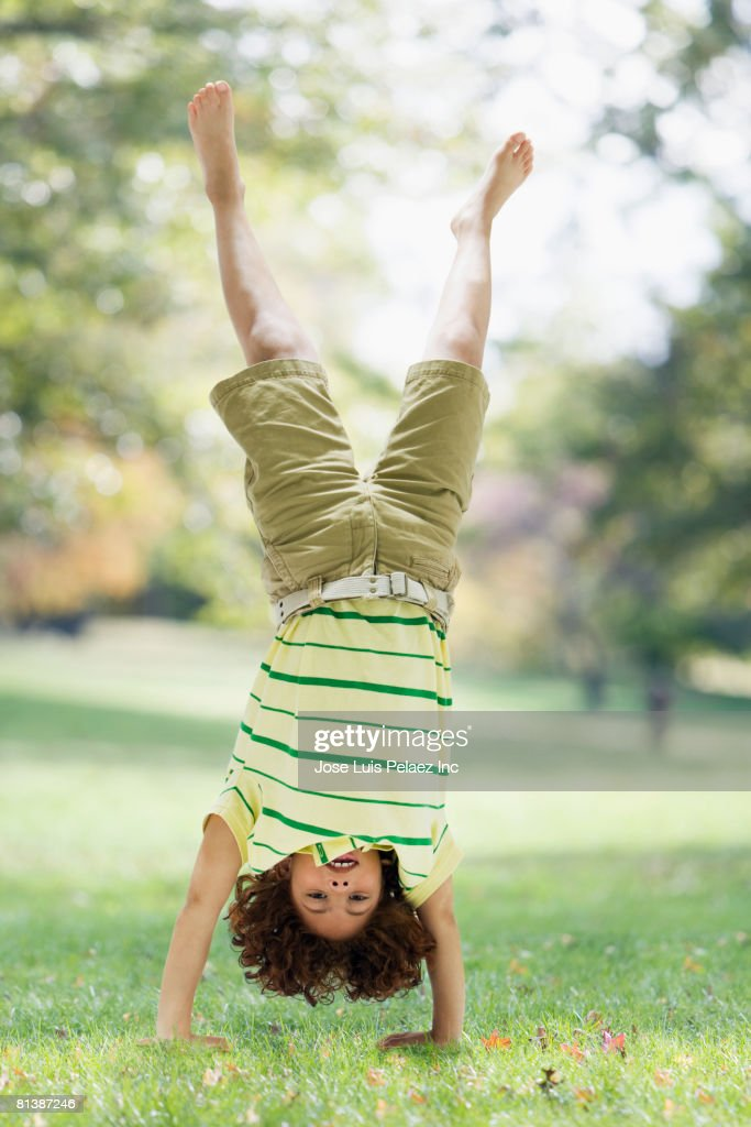Mixed Race boy performing handstand : Stock Photo