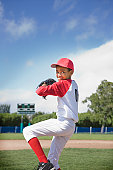 Mixed race boy pitching in baseball game