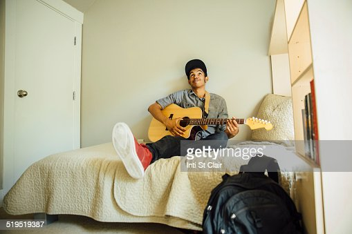 Mixed race boy playing guitar in bedroom   Stock Photo. Mixed Race Boy Playing Guitar In Bedroom Stock Photo   Getty Images