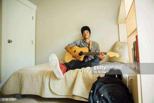 Mixed race boy playing guitar in bedroom