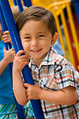 Mixed race boy playing in playground