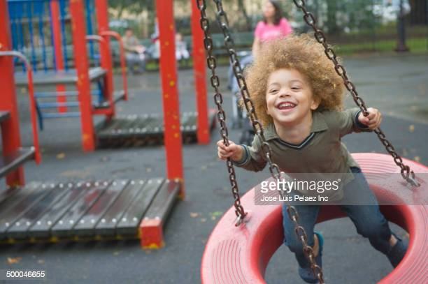 Mixed race boy playing on playground