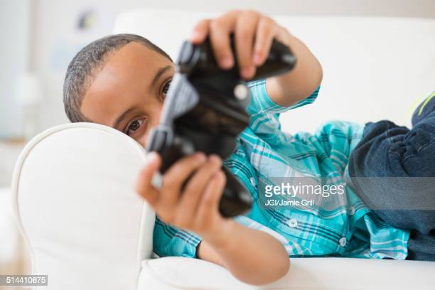 Mixed race boy playing video games