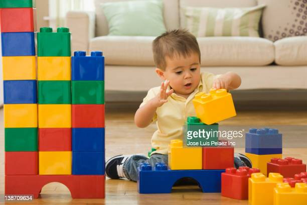 Mixed race boy playing with building blocks