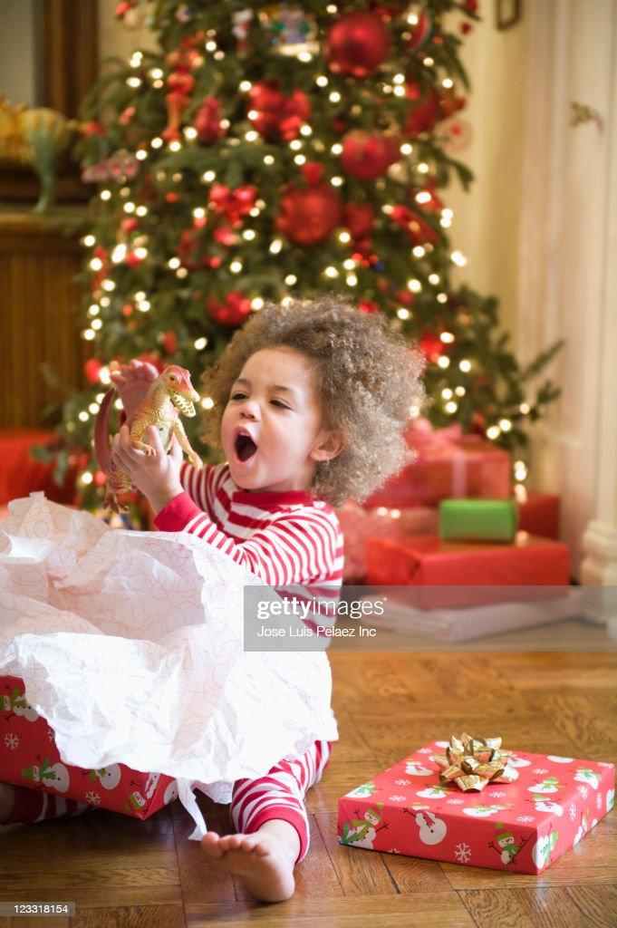 Mixed race boy playing with Christmas gift : Stock Photo