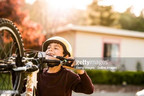 Mixed race boy playing with mountain bike