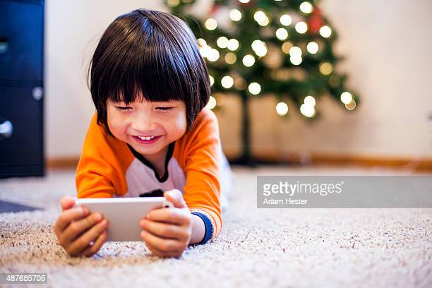 Mixed race boy playing with smart phone in living room