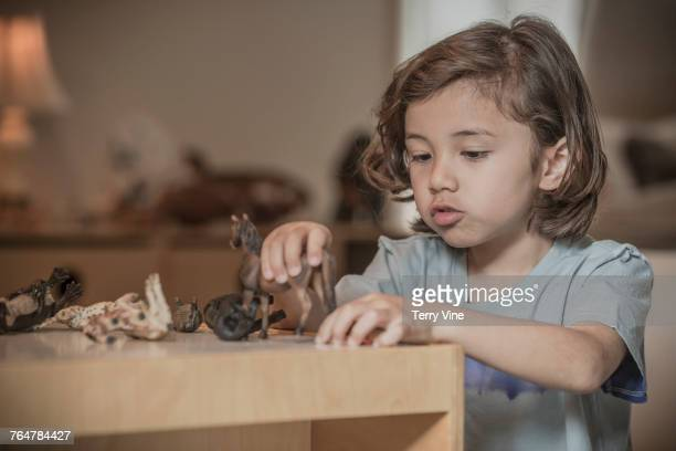 Mixed race boy playing with toy animals