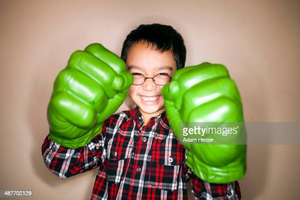Mixed race boy playing with toy boxing gloves