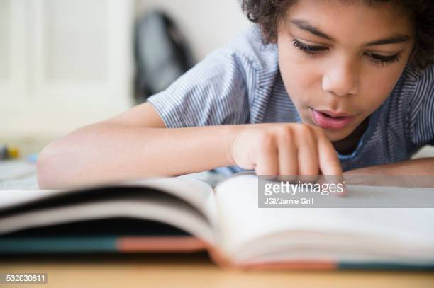 Mixed race boy reading book at desk