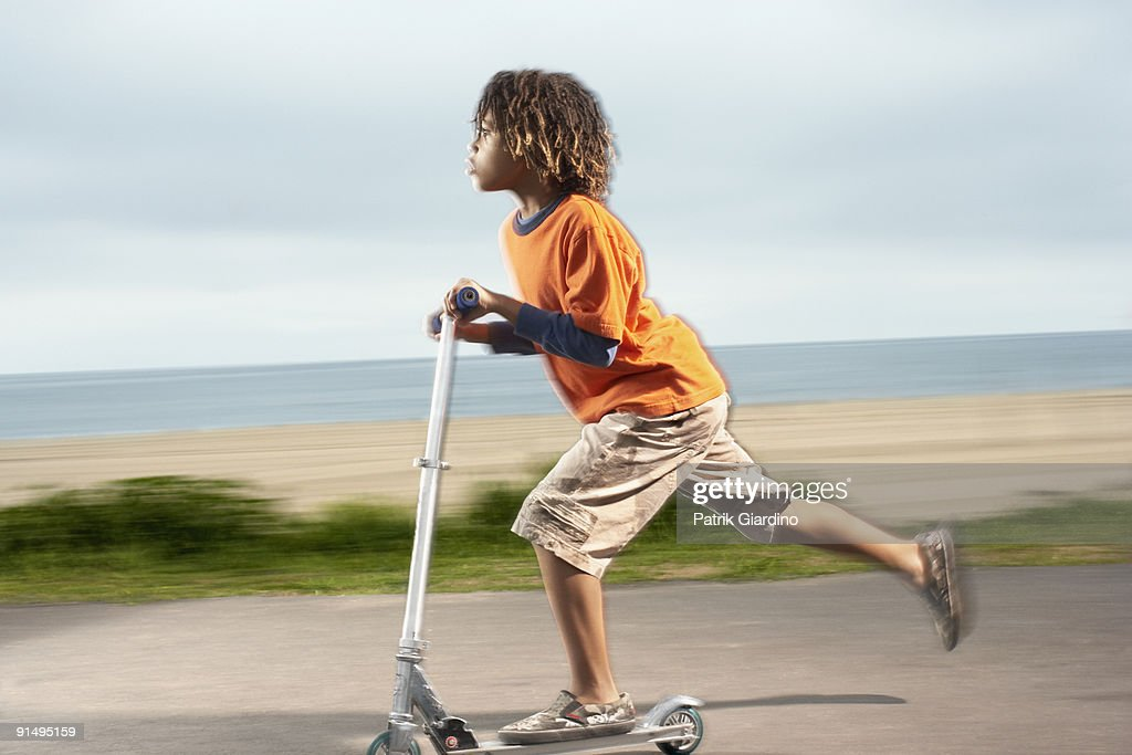 Mixed Race boy riding foot-powered scooter