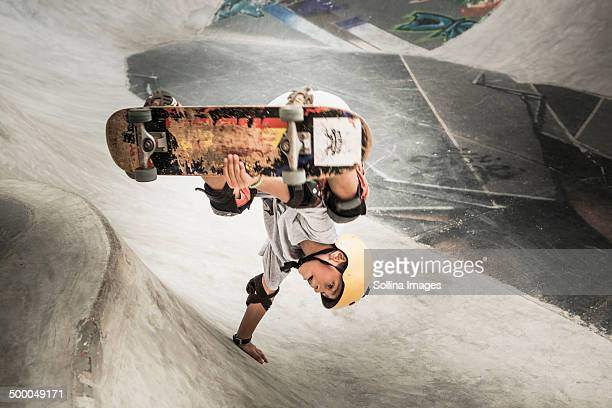 Mixed race boy riding skateboard in skate park