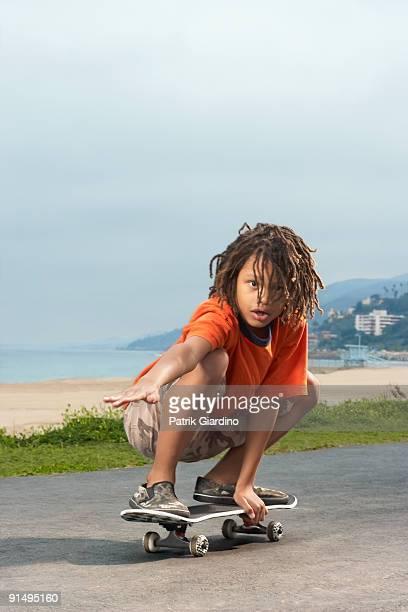 Mixed Race boy riding skateboard