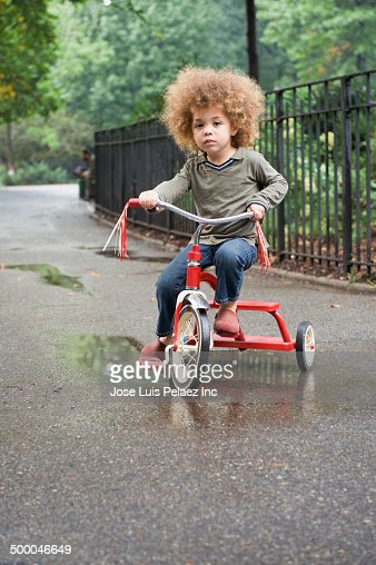 Mixed race boy riding tricycle in park