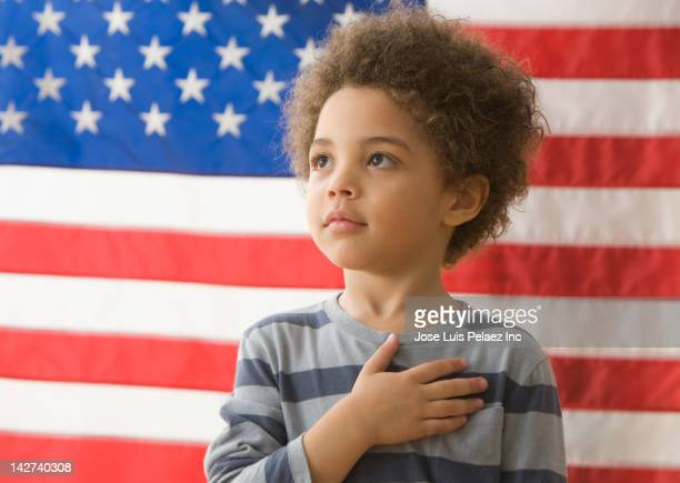 Mixed race boy saying the pledge of allegiance