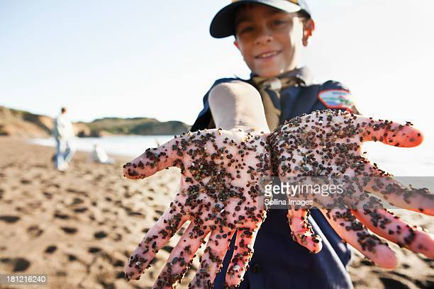 Mixed race boy showing dirty hands on beach