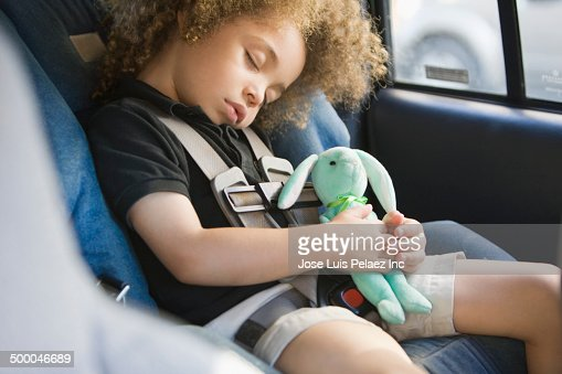Mixed race boy sleeping in car seat