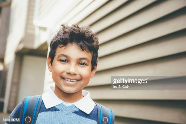 Mixed race boy smiling near house