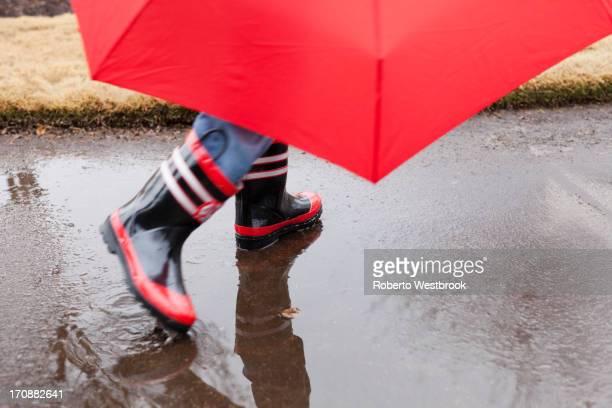 Mixed race boy splashing in rainboots