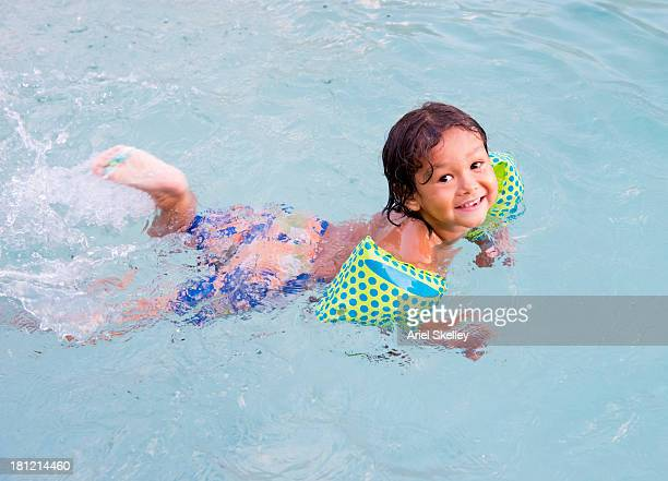 Mixed race boy swimming with floaters in pool