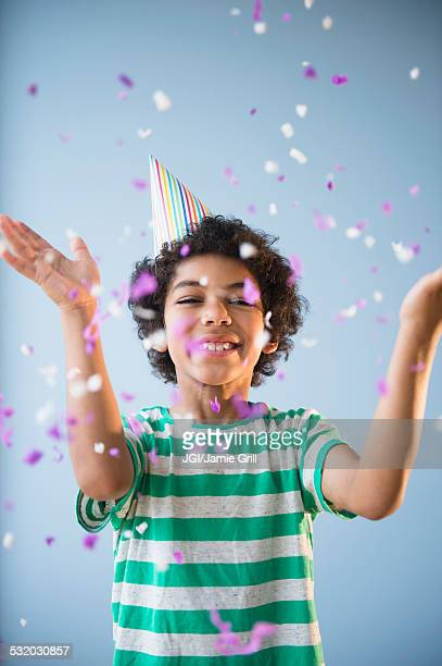 Mixed race boy throwing confetti at party