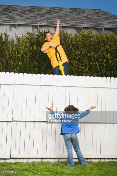 Mixed Race boy trying to jump fence with pogo stick