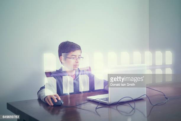 Mixed race boy using computer with holographic files