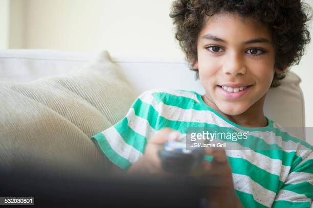 Mixed race boy watching television on sofa