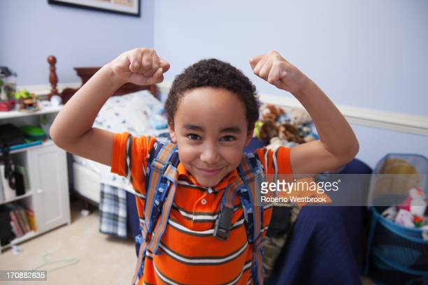 Mixed race boy wearing backpack in bedroom