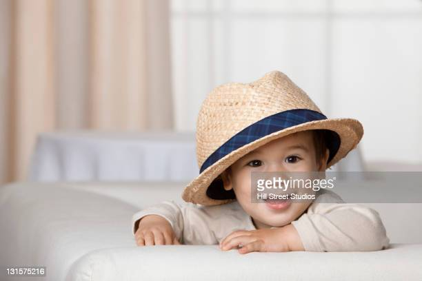 Mixed race boy wearing oversized hat