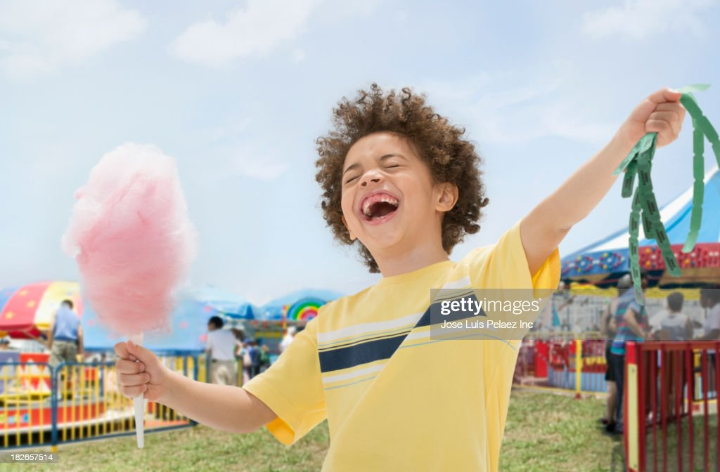 Mixed race boy with cotton candy and prize tickets at fair