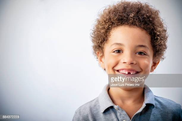 Mixed race boy with curly hair and missing tooth smiling