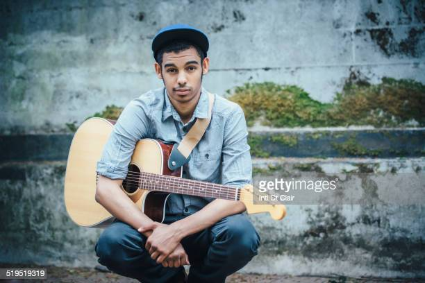 Mixed race boy with guitar crouching on urban sidewalk