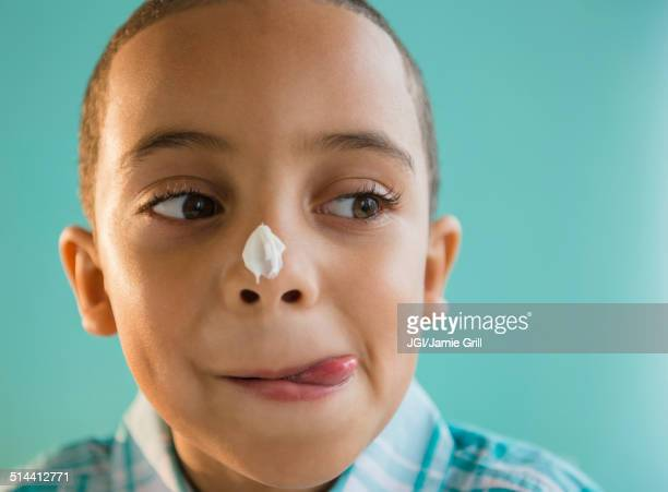 Mixed race boy with icing on nose