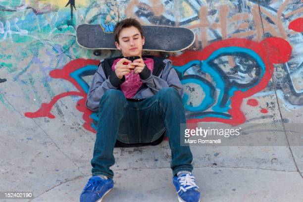 Mixed race boy with skateboard text messaging on cell phone
