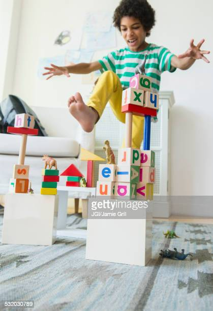 Mixed race boy wrecking wooden block city in living room
