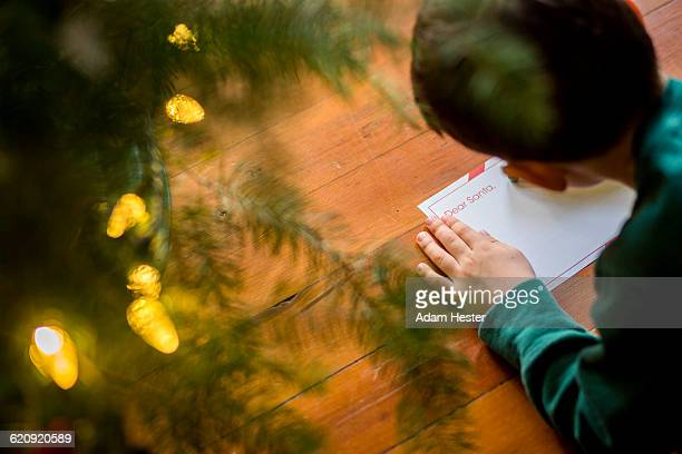 Mixed race boy writing letter to Santa